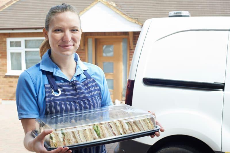 Photographie d'un traiteur qui livre au client des sandwichs